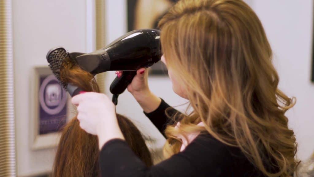 Woman having her hair blow dried