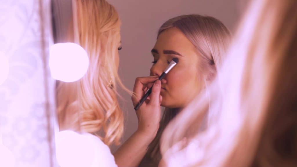 Professional makeup artist applying eye shadow.